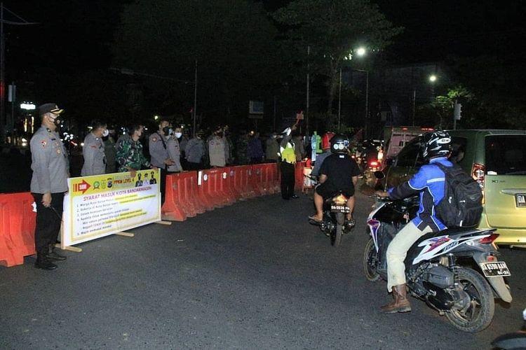 Petugas menghalau kendaraan yang hendak masuk Kota Banjarmasin dan dipaksa putar balik dalam penyekatan PPKM pada, Jumat (20/8/2021) malam.