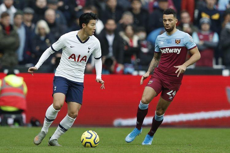 Penyerang Tottenham Hotspur Son Heung-Min (kiri) dijaga bek West Ham United, Ryan Fredericks, dalam laga antara West Ham United vs Tottenham Hotspur di Stadion London, di London timur, pada 23 November 2019.