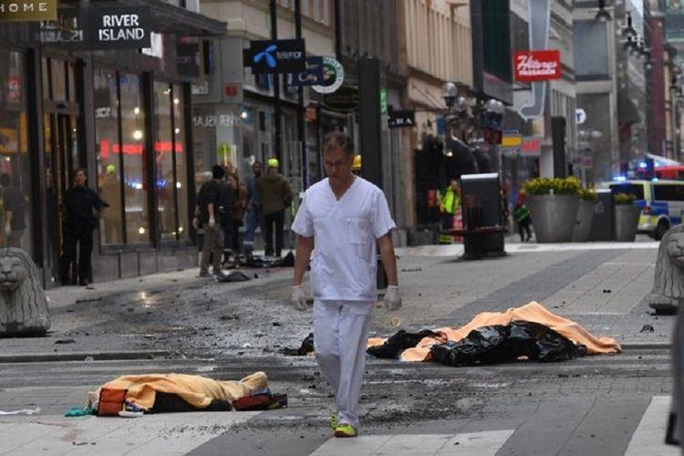 Petugas medis berjalan di lokasi kejadian di luar toko serba ada Ahlens, Stockholm, Swedia, pascaserangan teror truk pada Jumat (7/4/2017). Setidaknya empat orang tewas akibat serangan itu.