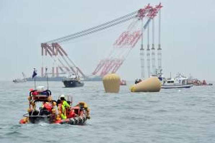Crane dari kilang lepas pantai, Jumat (18/4/2014), telah berada di lokasi tenggelamnnya kapal feri Sewol di perairan di sekitar pulau resor Jeju, Korea Selatan. Hingga Jumat malam, 28 penumpang kapal dipastikan tewas, 179 selamat, dan 268 orang masih belum ditemukan.