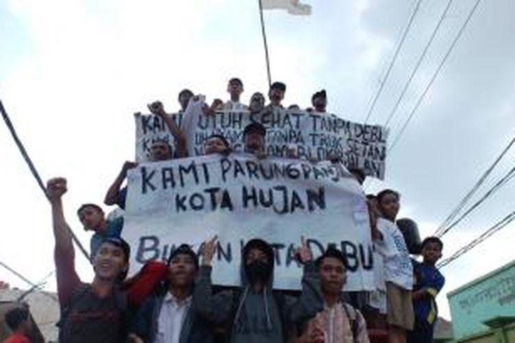 Ratusan warga dari 11 desa yang berada di wilayah Kecamatan Parung Panjang, Kabupaten Bogor, berunjuk rasa dengan memblokir Jalan Raya Parung Panjang. Massa pendemo juga sempat menahan dan menduduki mobil truk pengangkut batu dan pasir. K97-14