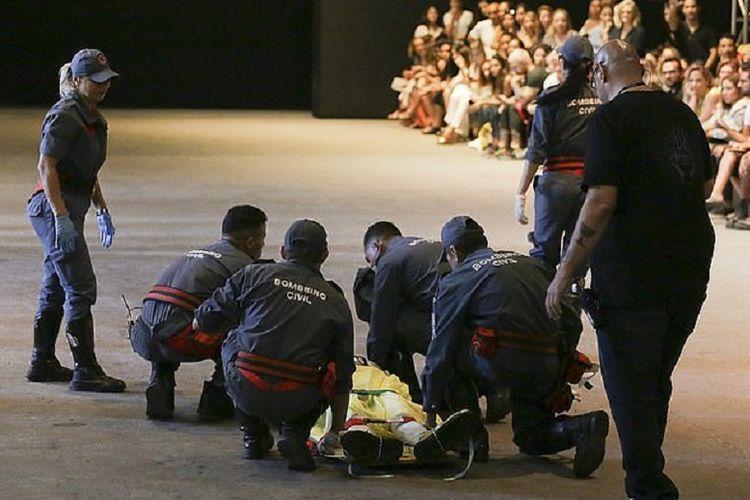 Petugas medis berusaha memberikan pertolongan dan mengembalikan kesadaran model Tales Soares (26) yang mendadak ambruk saat memperagakan busana di Sao Paulo, Brasil.