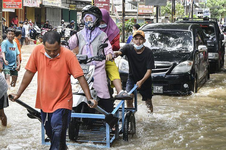 Dua orang pengendara motor menggunakan jasa gerobak untuk melintasi banjir di Jalan Bosih, Cibitung, Kabupaten Bekasi, Jawa Barat, Senin (8/2/2021). Menurut warga banjir menggenangi wilayah tersebut pada pukul 05.00 WIB akibat luapan aliran kali Jambe.