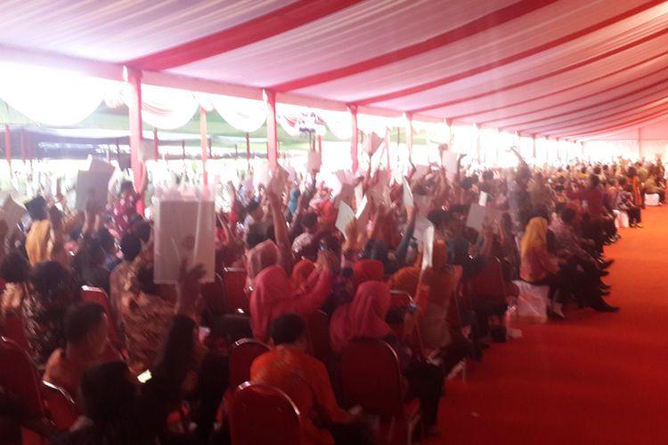 Ribuan warga Jawa Timur saat menunjukkan sertifikat tanah yang baru saja didapatkannya kepada Presiden Joko Widodo di Lapangan Brawijaya, Rampal, Kota Malang, Rabu (24/5/2017).