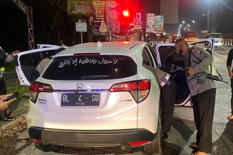 Polisi menggeledah mobil ZR pelaku teror putri Bupati Brebes yang berhasil diamankan di perempatan lampu merah Kota Tegal, Jawa Tengah, Minggu (18/4/2021) malam. (Istimewa)
