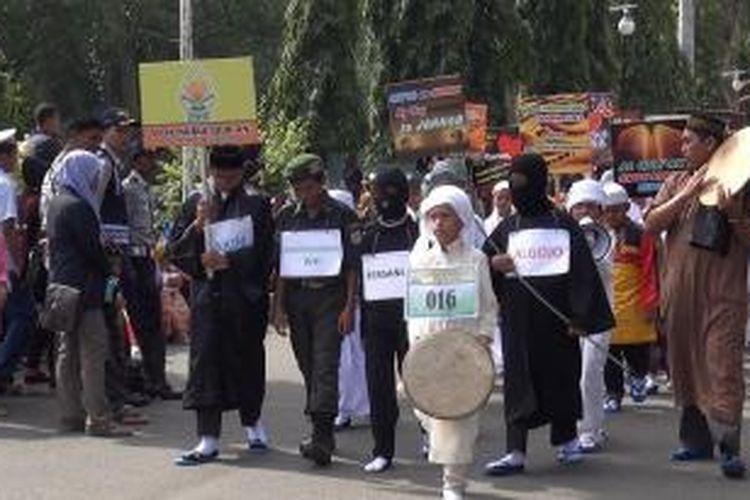 Peserta Karnaval Muharam mengenakan pakaian petugas uqubat cambuk saat memeriahkan karnaval Muharram pada perayaan pergantian tahun baru Hijriah di Banda Aceh, Sabtu (25/10/2014).