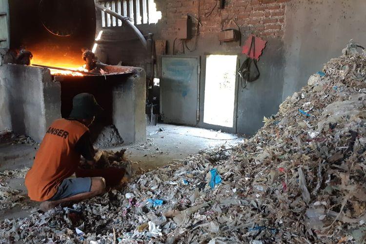 Pekerja mengambil sampah plastik impor untuk bahan bakar tungku pemasak kedelai pada industri tahu di Desa Tropodo, Sidoarjo, Selasa (18/6/2019).