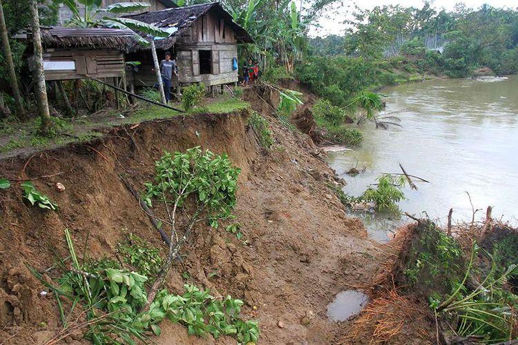 Sejumlah warga melihat rumah yang hampir amblas akibat erosi sungai di Desa Meutulang, Kecamatan Pantoe Reu, Aceh Barat, Aceh, Selasa (19/11/2019). Dampak banjir yang terjadi di Kabupaten setempat mengakibatkan amblasnya tebing sungai sepanjang 150 meter pada Sabtu (16/11).