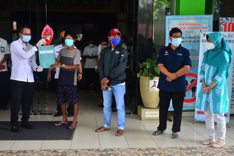 Plt Bupati Kudus Hartopo (kiri) memberikan surat keterangan negatif COVID-19 kepada salah satu pasien di RSUD Loekmono Hadi, Kudus, Jawa Tengah, Kamis (14/5/2020). Sebanyak empat pasien yang terkonfirmasi positif COVID-19 yakni pemudik dan tenaga kesehatan dinyatakan sembuh setelah menjalani perawatan. ANTARA FOTO/Yusuf Nugroho/aww.