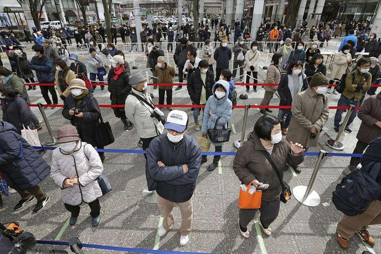 Warga dengan masker pelindung menjaga dari penularan virus COVID-19, mengantre secara berjarak untuk menyaksikan api Olimpiade saat tur Reli Api Olimpiade Tokyo 2020 di Fukushima, Jepang, Selasa (24/3/2020).