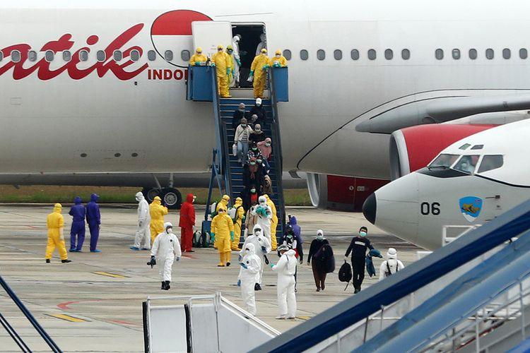 Sebanyak 250 WNI yang dievakuasi dari Kota Wuhan, China turun dari pesawat setibanya di Bandara Hang Nadim, Batam, Kepulauan Riau, Minggu (2/2/2020). WNI yang dievakuasi dari Wuhan tersebut kemudian diterbangkan kembali menuju Ranai, Natuna untuk menjalani observasi.