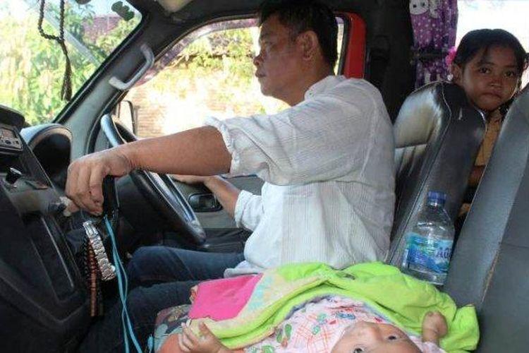 Nurul Mukminin sopir angkot trayek Mangkang-Johar memegang setir, Jumat (7/2/2020), ditemani bayinya Bilqis Choirun Nisa dan anak tertua, Balqis Choirun Najwa.