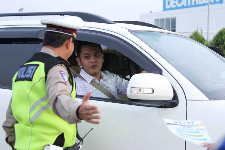Petugas kepolisian mengarahkan kendaraan yang melintas saat uji coba sistem ganjil genap di Pintu Tol Kunciran 2, Tangerang, Banten, Senin (16/4/2018). Kepala Badan Pengelola Transportasi Jabodetabek (BPTJ) Bambang Prihartono menargetkan, kebijakan sistem ganjil-genap di tol Tangerang-Jakarta bisa mengurangi kepadatan menuju Jakarta hingga 50 persen.