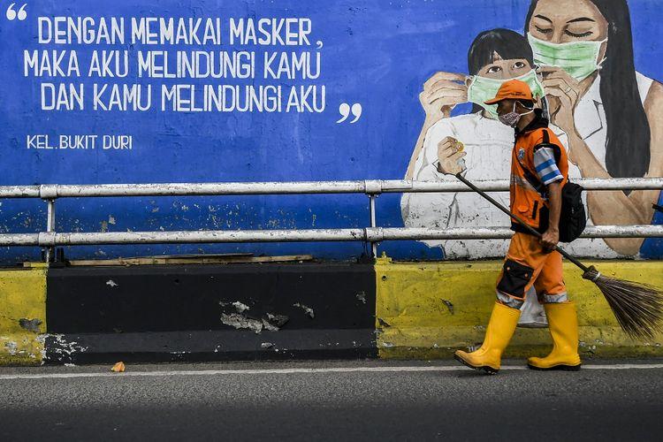Petugas kebersihan melintas di depan mural tentang pandemi Covid-19 di Kawasan Tebet, Jakarta, Selasa (15/9/2021).