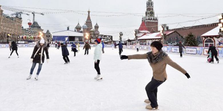 Warga menikmati hamparan es temporari yang dipasang di tengah Lapangan Merah, di Kota Moskwa, Rabu (14/12/2016).