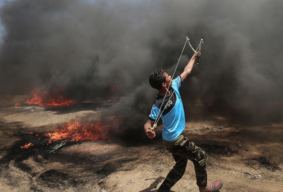 Seorang warga Palestina menyerang dengan ketapel saat terjadi bentrokan dengan pasukan Israel di dekat perbatasan antara jalur Gaza dan Israel, di sebelah timur Kota Gaza, Senin (14/5/2018). Otoritas Palestina menyebut pasukan Israel telah menewaskan 55 orang dan melukai 2.700 orang dalam aksi protes dan bentrokan menentang pembukaan Kedutaan Besar Amerika Serikat di Yerusalem.. (AFP PHOTO/SAID KHATIB)