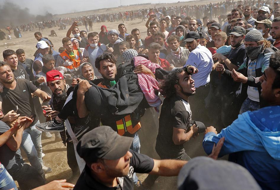 Warga Palestina mengangkat seorang korban terluka saat terjadi bentrokan dengan pasukan Israel di dekat perbatasan antara jalur Gaza dan Israel, di sebelah timur Kota Gaza, Senin (14/5/2018). Otoritas Palestina menyebut pasukan Israel telah menewaskan 55 orang dan melukai 2.700 orang dalam aksi protes dan bentrokan menentang pembukaan Kedutaan Besar Amerika Serikat di Yerusalem. (AFP PHOTO/THOMAS COEX)