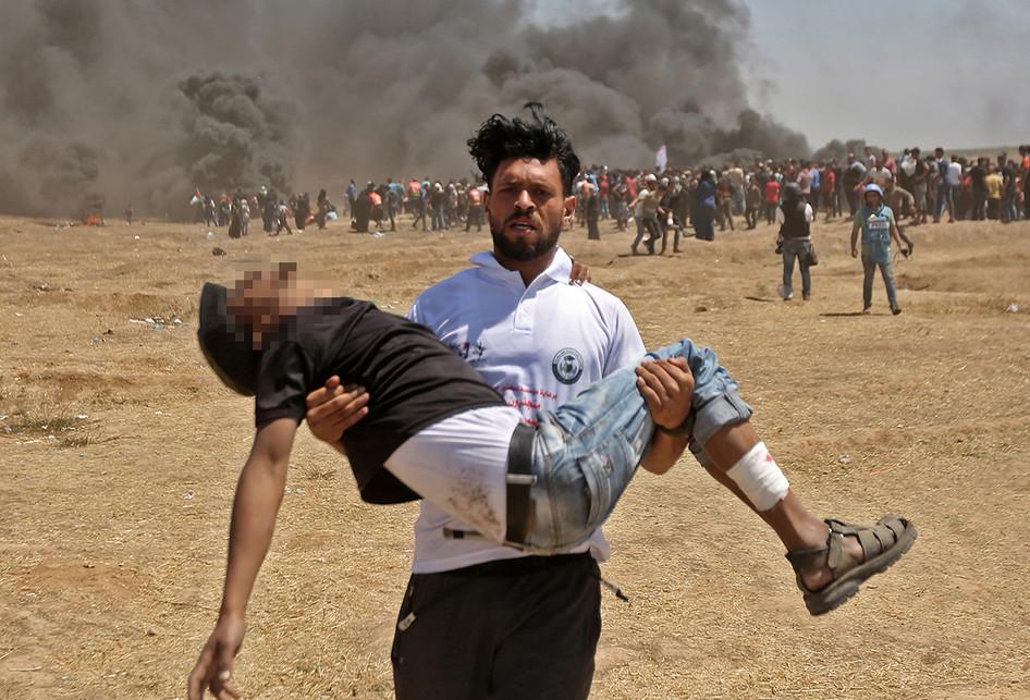 Warga Palestina mengangkat seorang korban saat terjadi bentrokan dengan pasukan Israel di dekat perbatasan antara jalur Gaza dan Israel, di sebelah timur Kota Gaza, Senin (14/5/2018). Otoritas Palestina menyebut pasukan Israel telah menewaskan 55 orang dan melukai 2.700 orang dalam aksi protes dan bentrokan menentang pembukaan Kedutaan Besar Amerika Serikat di Yerusalem.. (AFP PHOTO/MAHMUD HAMS)