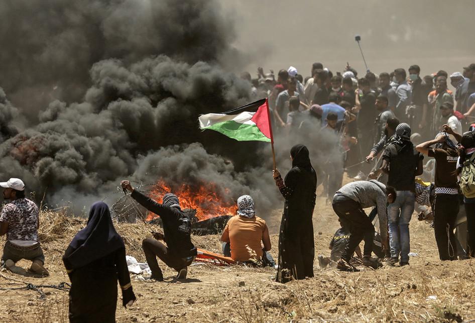 Seorang perempuan warga Palestina memegang bendera negaranya saat terjadi bentrokan dengan pasukan Israel di dekat perbatasan antara jalur Gaza dan Israel, di sebelah timur Kota Gaza, Senin (14/5/2018). Otoritas Palestina menyebut pasukan Israel telah menewaskan 55 orang dan melukai 2.700 orang dalam aksi protes dan bentrokan menentang pembukaan Kedutaan Besar Amerika Serikat di Yerusalem.. (AFP PHOTO/MAHMUD HAMS)