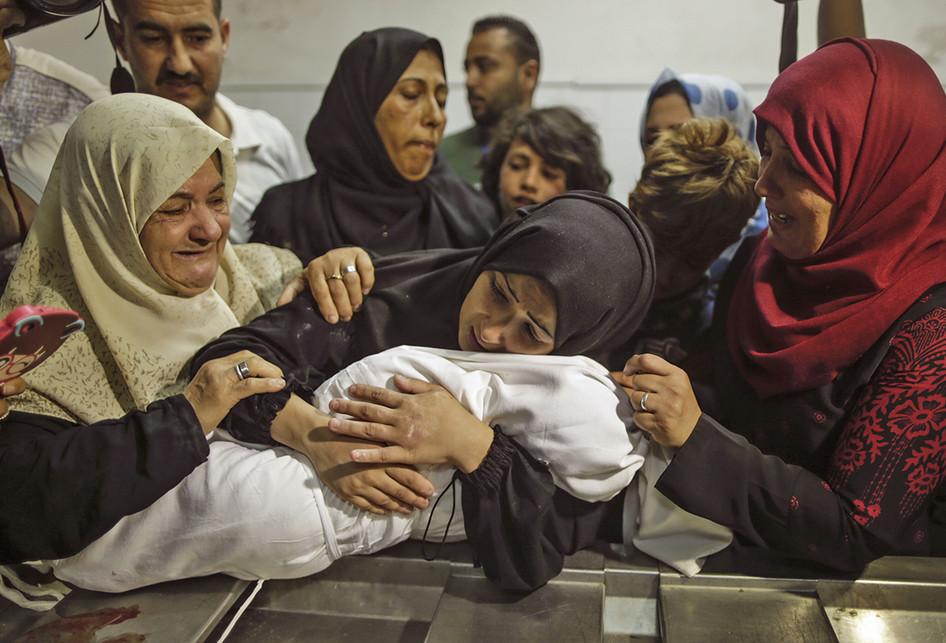 Luapan duka Ibu dari Leila al-Ghandour (tengah), bayi berumur 8 bulan asal Palestina yang tewas akibat insiden bentrokan dengan pasukan Israel di dekat perbatasan antara jalur Gaza dan Israel, di sebelah timur Kota Gaza, Senin (14/5/2018). Otoritas Palestina menyebut pasukan Israel telah menewaskan 55 orang dan melukai 2.700 orang dalam aksi protes dan bentrokan menentang pembukaan Kedutaan Besar Amerika Serikat di Yerusalem.. (AFP PHOTO/MAHMUD HAMS)