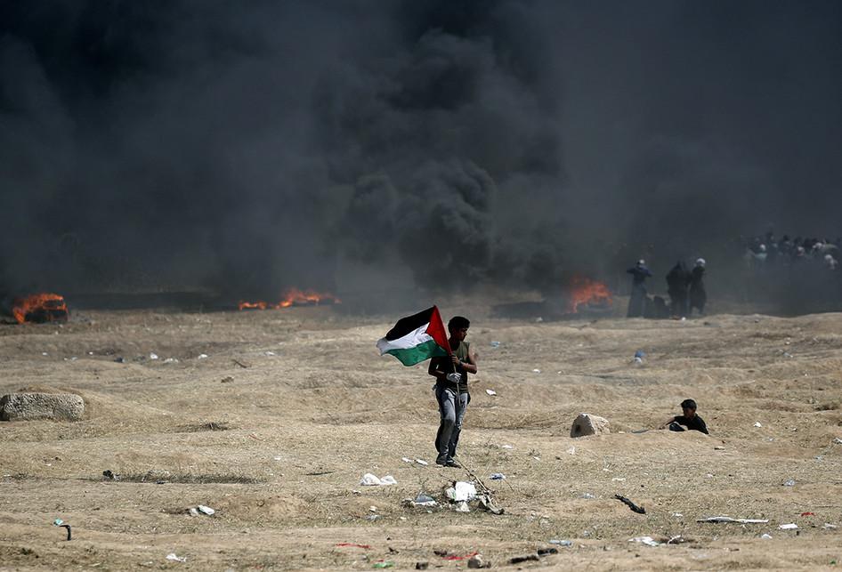 Seorang pria warga Palestina memegang bendera negaranya saat terjadi bentrokan dengan pasukan Israel di dekat perbatasan antara jalur Gaza dan Israel, di sebelah timur Kota Gaza, Senin (14/5/2018). Otoritas Palestina menyebut pasukan Israel telah menewaskan 55 orang dan melukai 2.700 orang dalam aksi protes dan bentrokan menentang pembukaan Kedutaan Besar Amerika Serikat di Yerusalem.. (AFP PHOTO/THOMAS COEX)