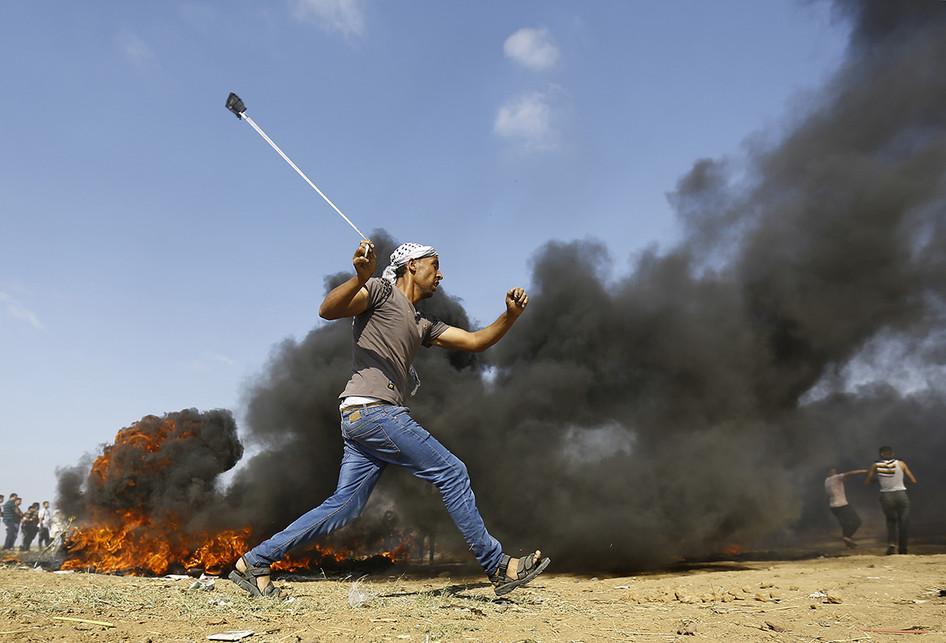 Seorang warga Palestina berupaya menyerang dengan batu saat terjadi bentrokan dengan pasukan Israel di dekat perbatasan antara jalur Gaza dan Israel, di sebelah timur Kota Gaza, Senin (14/5/2018). Otoritas Palestina menyebut pasukan Israel telah menewaskan 55 orang dan melukai 2.700 orang dalam aksi protes dan bentrokan menentang pembukaan Kedutaan Besar Amerika Serikat di Yerusalem.. (AFP PHOTO/MOHAMMED ABED)