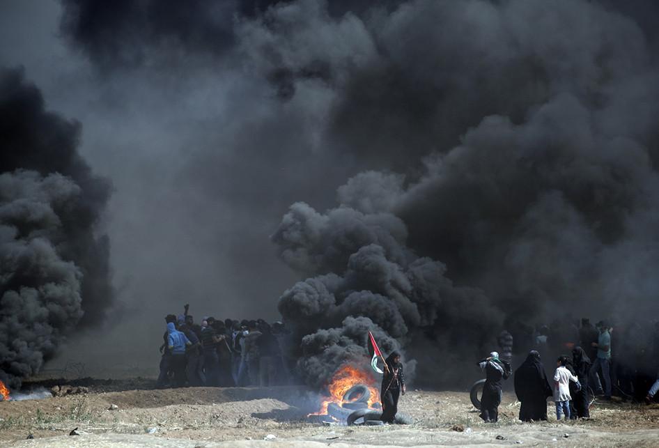 Warga Palestina membakar ban saat terjadi bentrokan dengan pasukan Israel di dekat perbatasan antara jalur Gaza dan Israel, di sebelah timur Kota Gaza, Senin (14/5/2018). Otoritas Palestina menyebut pasukan Israel telah menewaskan 55 orang dan melukai 2.700 orang dalam aksi protes dan bentrokan menentang pembukaan Kedutaan Besar Amerika Serikat di Yerusalem.. (AFP PHOTO/THOMAS COEX)