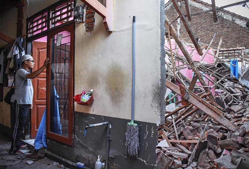 Seorang laki-laki melihat rumahnya yang sebagian temboknya roboh pascagempa bumi di Dusun Lendang Bajur, Kecamatan Gunungsari, Lombok Barat, NTB, Senin (6/8/2018). Badan Penanggulangan Bencana Daerah (BPBD) NTB mendapatkan laporan sementara jumlah korban meninggal dunia akibat gempa bumi berkekuatan 7 Skala Richter sampai dengan pukul 03.20 Wita, Senin ini, sebanyak 82 orang.
